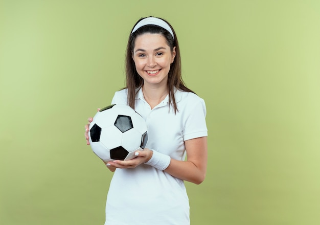 明るい壁の上に幸せで前向きに立って笑顔のサッカーボールを保持しているヘッドバンドの若いフィットネス女性