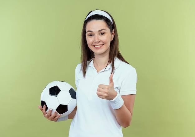 明るい壁の上に立って親指を見せて笑ってサッカーボールを保持しているヘッドバンドの若いフィットネス女性