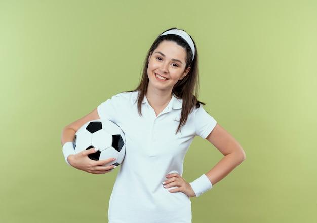 明るい壁の上に幸せで前向きに立って笑顔のヒップで腕とサッカーボールを保持しているヘッドバンドの若いフィットネス女性