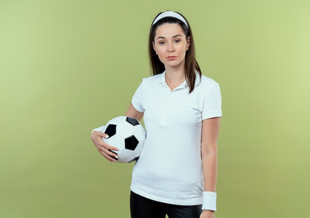 光の壁の上に立っている深刻な自信を持って表情でサッカーボールを保持しているヘッドバンドの若いフィットネス女性