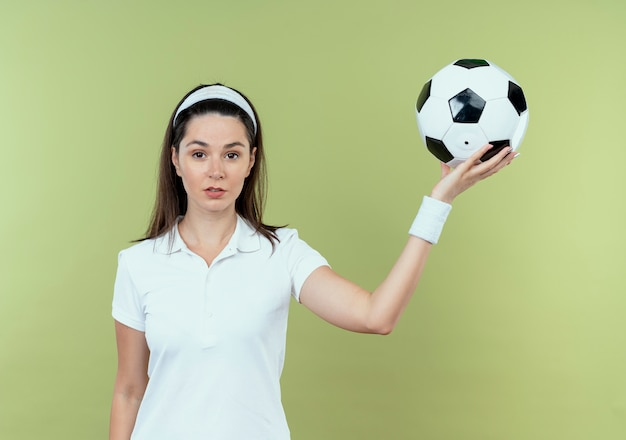明るい壁の上に立っている深刻な顔でサッカーボールを保持しているヘッドバンドの若いフィットネス女性