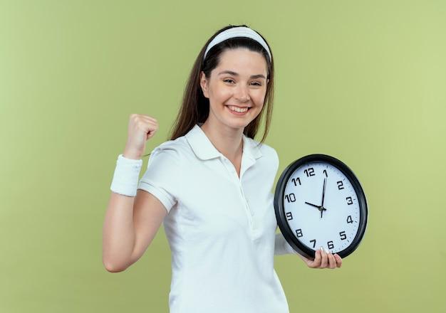 明るい背景の上に立って幸せで興奮して拳を握り締める壁時計を保持しているヘッドバンドの若いフィットネス女性