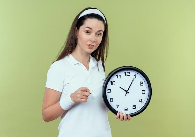 Молодая фитнес-женщина в головной повязке, держащая настенные часы, указывая пальцем, улыбаясь, стоя над светлой стеной
