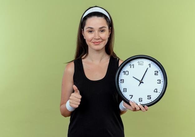 Молодая фитнес-женщина в головной повязке, держащая настенные часы, показывает палец вверх, улыбаясь, стоя над светлой стеной