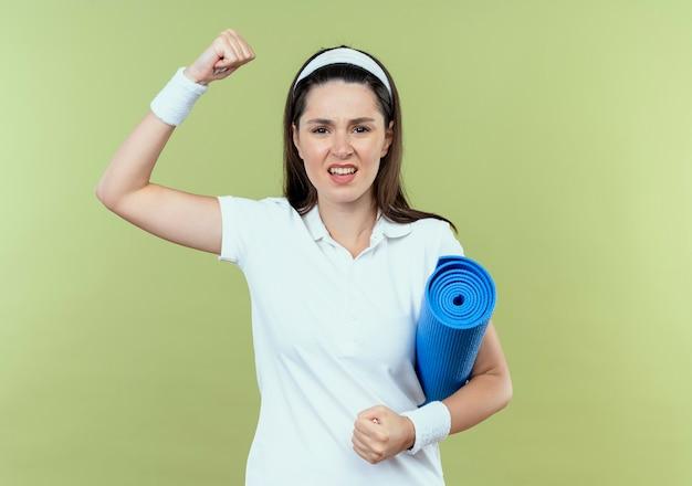 明るい背景の上に立っている怒っている顔でカメラを見て拳を上げるヨガマットを保持しているヘッドバンドの若いフィットネス女性