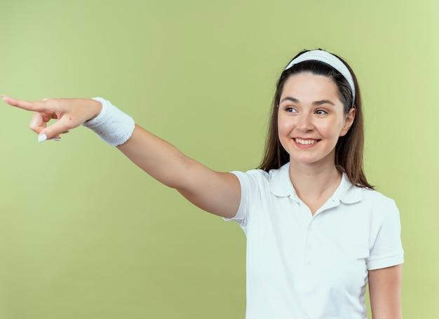 Молодая фитнес-женщина в ободке смотрит в сторону, указывая на что-то с улыбкой на лице, стоя над светлой стеной