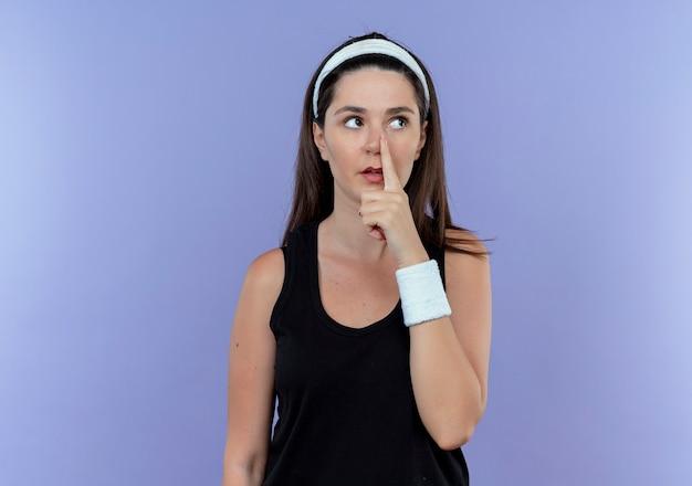 青い背景の上に立っている彼女の鼻に指を指して脇を見ているヘッドバンドの若いフィットネス女性