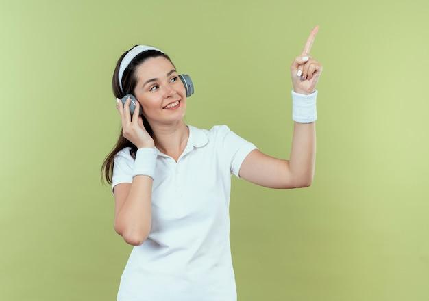 ヘッドバンドの若いフィットネス女性は、明るい背景の上に立って笑って横に指で指して脇を見て