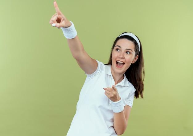 ヘッドバンドの若いフィットネス女性は、明るい背景の上に立って微笑んで横に指で指して脇を見て