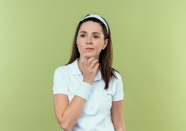 明るい背景の上に立っている顔の思考に物思いにふける表情であごに手を脇に見ているヘッドバンドの若いフィットネス女性