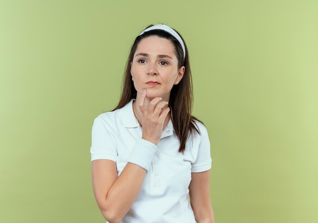 軽い壁の上に立っている顔の思考に物思いにふける表情で顎に手を脇に見ているヘッドバンドの若いフィットネス女性
