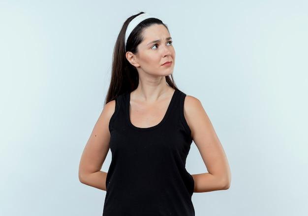 白い背景の上に立っている顔に物思いにふける表情で脇を探しているヘッドバンドの若いフィットネス女性
