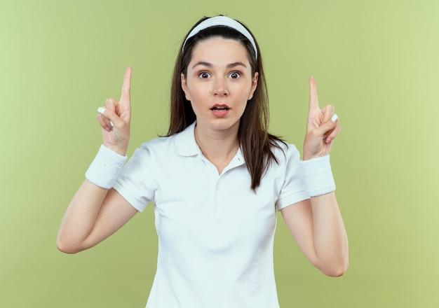 카메라를보고 머리띠에 젊은 피트 니스 여자는 밝은 배경 위에 서있는 새로운 아이디어를 갖는 검지 손가락을 보여주는 놀란