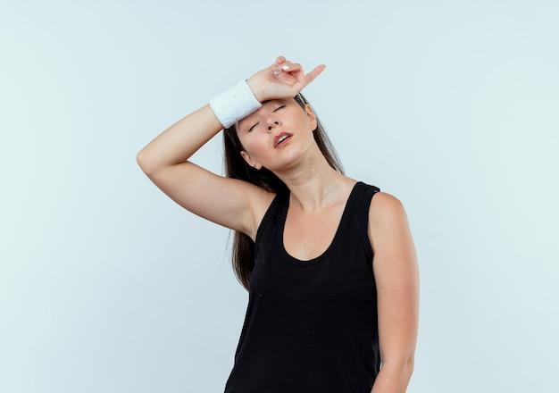 白い壁の上に立ってトレーニング後に疲れて疲れているように見えるヘッドバンドの若いフィットネス女性