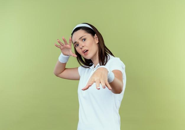 明るい背景の上に立っている恐怖の表情でカメラを見て手で防衛ジェスチャーを作るヘッドバンドの若いフィットネス女性