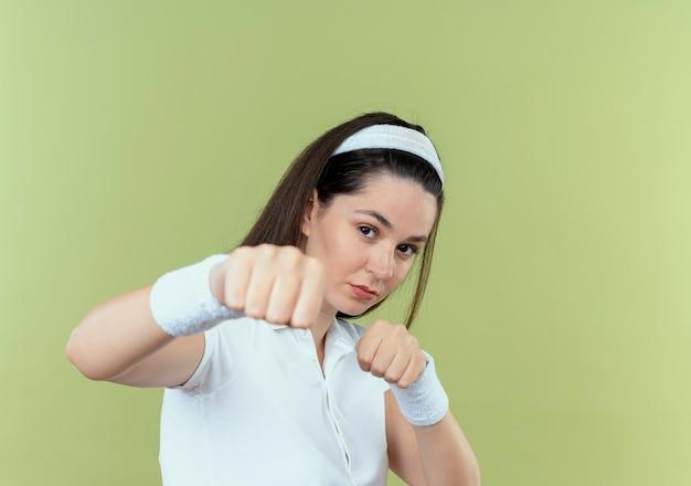 밝은 배경 위에 서있는 카메라를 주먹으로 가리키는 권투 선수처럼 포즈를 취하는 머리띠에 젊은 피트 니스 여자