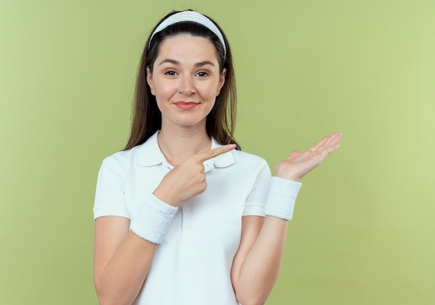 軽い壁の上に立って微笑んで横に指で指している彼女の手の腕で何かを提示するヘッドバンドの若いフィットネス女性