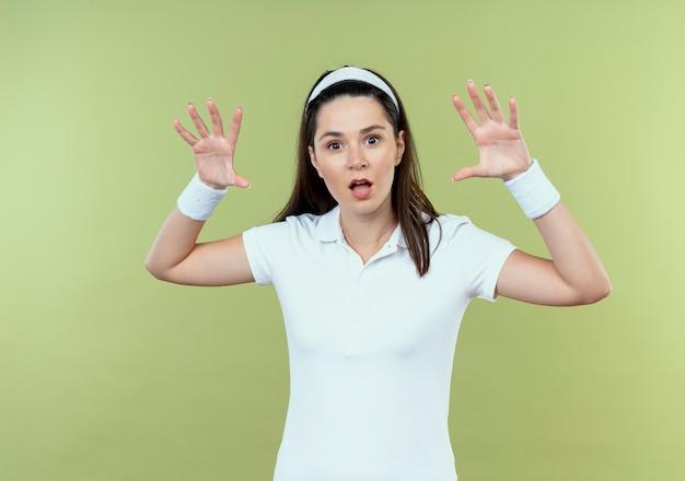 明るい背景の上に立っているカメラを見て脅して手を上げるヘッドバンドの若いフィットネス女性