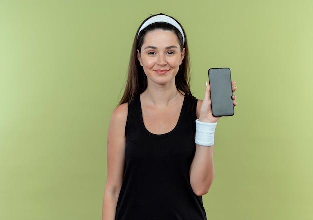밝은 배경 위에 서있는 카메라를보고 자신감 미소 스마트 폰을 보여주는 머리띠에 젊은 피트 니스 여자