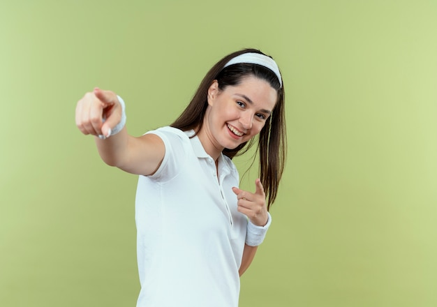 밝은 벽 위에 서있는 손가락으로 유쾌하게 가리키는 머리띠에 젊은 피트 니스 여자