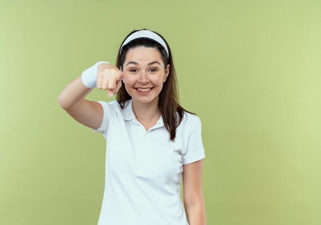 明るい背景の上に立っているカメラに指で元気に指して笑っているヘッドバンドの若いフィットネス女性