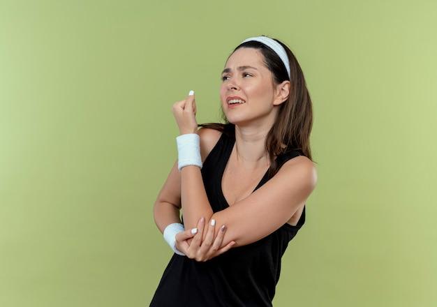 Молодая женщина фитнеса в повязке на голову, касаясь ее локтя, чувствуя боль, стоя над светлой стеной