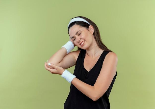 Молодая женщина фитнеса в повязке на голову, касаясь ее локтя с болью, стоя над светлой стеной