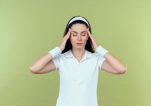 彼女の寺院に触れるヘッドバンドの若いフィットネス女性は、明るい背景の上に立って倦怠感を感じています