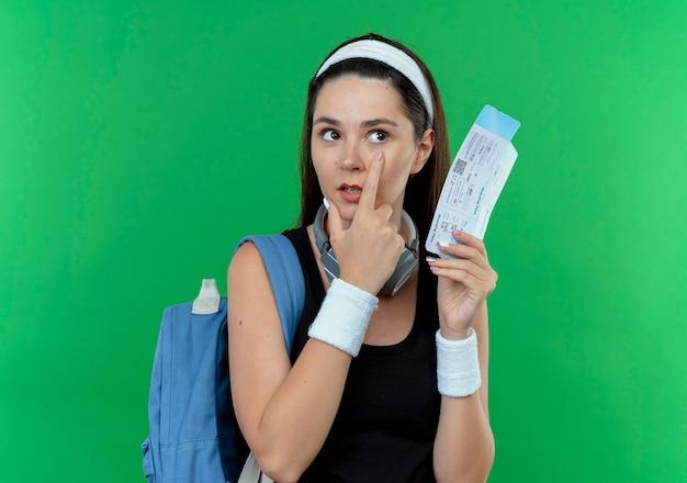 緑の背景の上に立っている彼女の目に指で指している航空券を保持しているバックパックとヘッドバンドの若いフィットネス女性