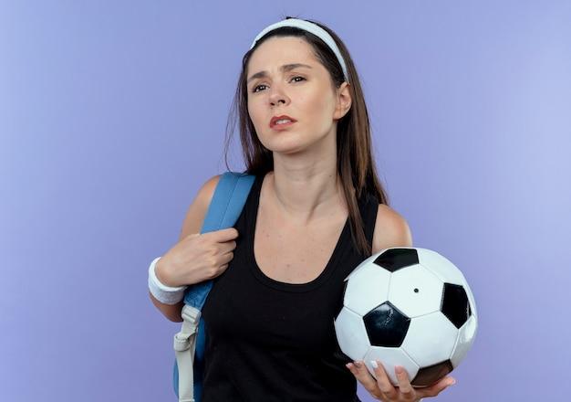 青い背景の上に立って混乱しているように見えるサッカーボールを保持しているバックパックとヘッドバンドの若いフィットネス女性