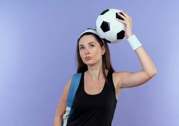 青い壁の上に立って自信を持って見える頭の上にサッカーボールを保持しているバックパックとヘッドバンドの若いフィットネス女性