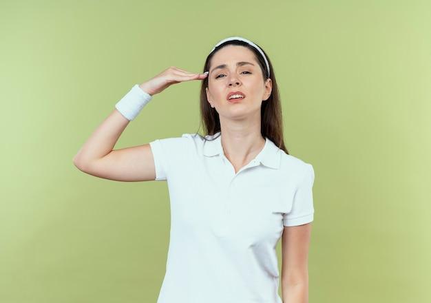 Молодая фитнес-женщина в повязке на голову с уверенным выражением лица салютует стоя над светлой стеной