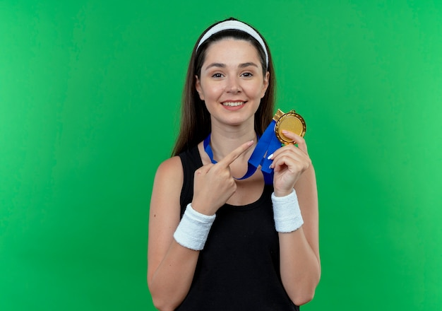 緑の背景の上に元気に立って笑顔でメダルを指で指して彼女の首の周りに金メダルを持つヘッドバンドの若いフィットネス女性