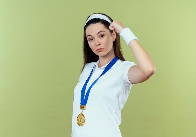 彼女の首の周りに金メダルを持ったヘッドバンドの若いフィットネス女性は、明るい背景の上に立って自信を持って拳を上げています