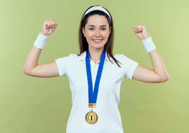 彼女の首の周りに金メダルを持ったヘッドバンドの若いフィットネス女性は、明るい壁の上に立って笑顔で幸せそうな顔に自信を持って拳を上げています