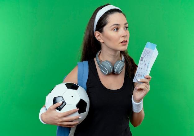 緑の背景の上に立って混乱して脇を見てサッカーボールと航空券を保持しているヘッドフォンとバックパックを持つヘッドバンドの若いフィットネス女性