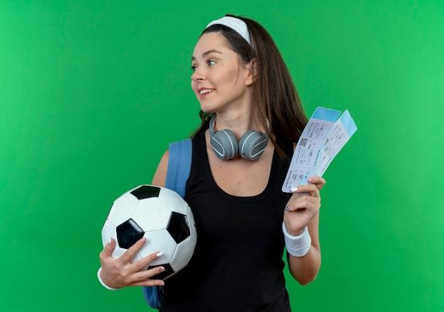 緑の背景の上に立って笑顔で脇を見てサッカーボールと航空券を保持しているヘッドフォンとバックパックとヘッドバンドの若いフィットネス女性