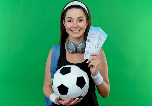 緑の壁の上に立って幸せそうな顔で笑ってサッカーボールと航空券を保持しているヘッドフォンとバックパックとヘッドバンドの若いフィットネス女性