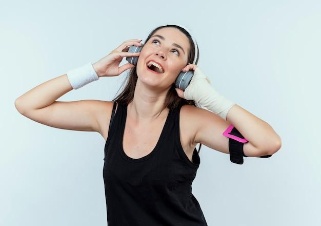 헤드폰 및 스마트 폰 완장 머리띠에 젊은 피트 니스 여자는 흰 벽 위에 서 그녀가 좋아하는 음악을 즐기는