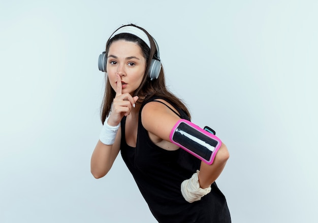 白い背景の上に立っている唇に指で沈黙のジェスチャーを作るヘッドフォンとスマートフォンのアームバンドとヘッドバンドの若いフィットネス女性