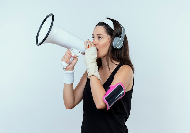 헤드폰 및 스마트 폰 완장이 흰 벽 위에 서있는 확성기를 외치는 머리띠에 젊은 피트 니스 여자