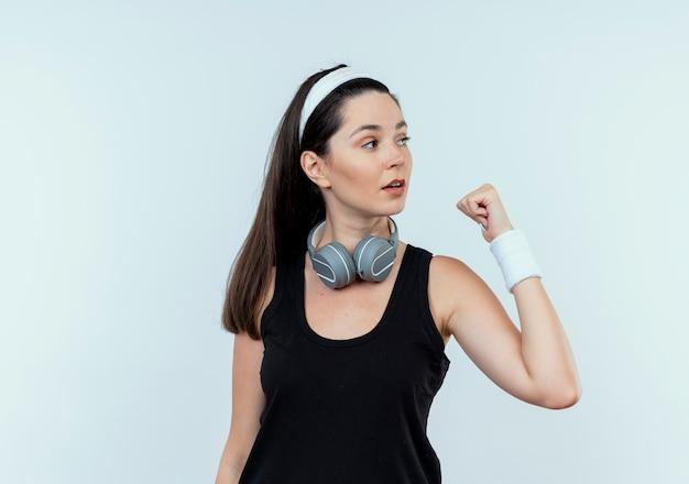 白い背景の上に立っているくいしばられた握りこぶしで脇を見てヘッドフォンでヘッドバンドの若いフィットネス女性