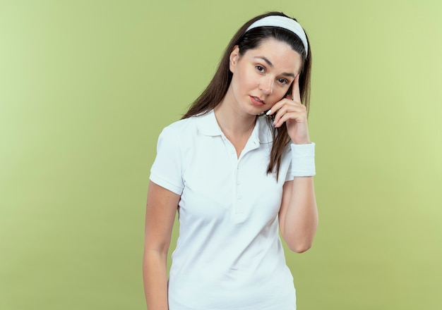 가벼운 벽 위에 서있는 얼굴 생각에 잠겨있는 표정으로 머리띠에 젊은 피트 니스 여자