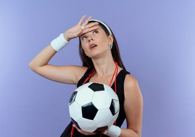 青い壁の上に立って疲れて見上げるサッカーボールを保持している首の周りの縄跳びとヘッドバンドの若いフィットネス女性