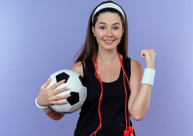 青い壁の上に幸せで前向きに立って幸せで前向きな拳を握りしめながらサッカーボールを保持している首の周りの縄跳びとヘッドバンドの若いフィットネス女性