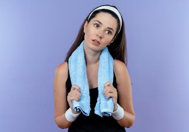 青い背景の上に立って疲れて退屈を脇に見て首の周りにタオルでヘッドバンドの若いフィットネス女性