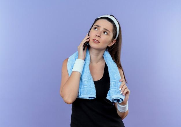 青い背景の上に立って困惑した携帯電話で話している首の周りのタオルとヘッドバンドの若いフィットネス女性