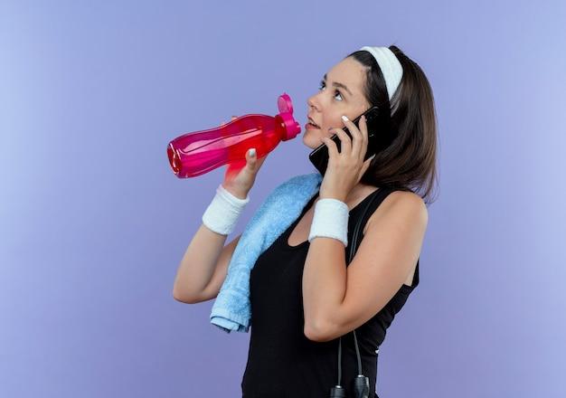 青い壁の上に立っている携帯電話で話している間彼女の肩の飲料水にタオルでヘッドバンドの若いフィットネス女性