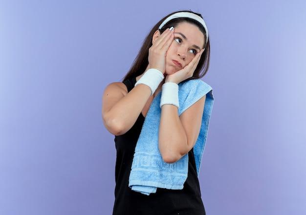 青い背景の上に立っている頬を吹くわざわざ脇を見て彼女の肩にタオルでヘッドバンドの若いフィットネス女性