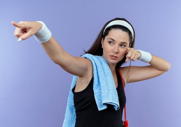 青い壁の上に立っている側に指と手を指して自信を持って見える彼女の肩にタオルでヘッドバンドの若いフィットネス女性